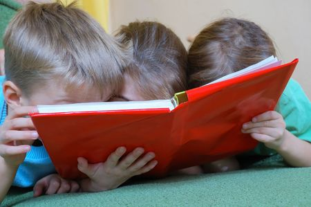 three 5 year old kid reading the same book Stock Photo - 5845137