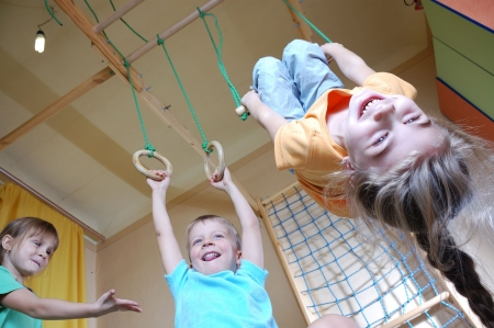 the trapeze: three happy 5 year old children playing together at home
