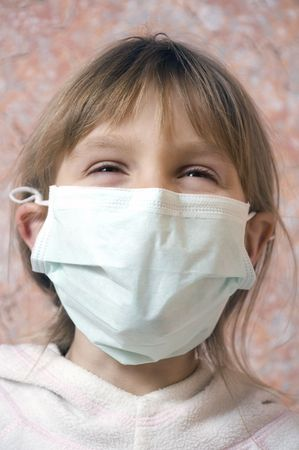 swine flu: laughing little girl wearing a protective mask