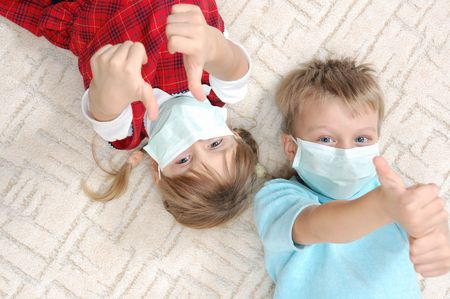children lying on the carpet with masks and their thimbs up photo