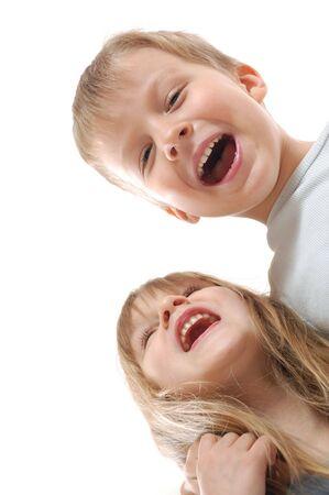 mejores amigas: los ni�os riendo felices pareja en el bakcground blanco Foto de archivo
