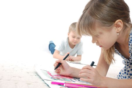 5 year old kids drawing and reading lying on the floor  photo