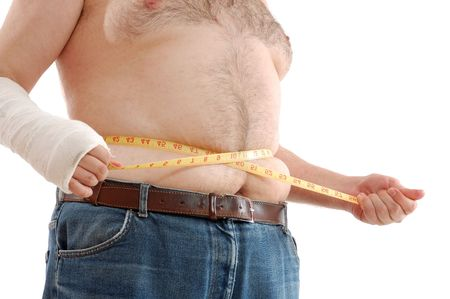 belly bandage: fat man measuring his belly against the white background Stock Photo