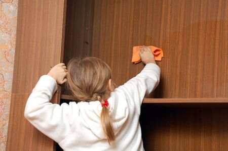 little girl cleaning the shelves with a wet cloth photo