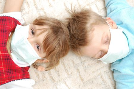 protective wear: little boy and girl wearing a protective mask Stock Photo