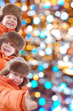 winter collage of happy 5 year old kids wearing the same brown hat and orange coat against the colorful light background photo