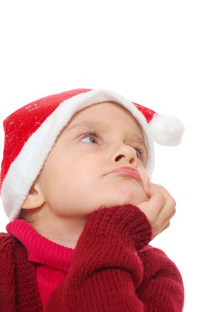 little dreamy girl wearing a Santa Clause hat looking up photo