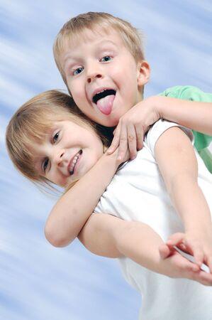 playful children couple against the blu bakcground photo