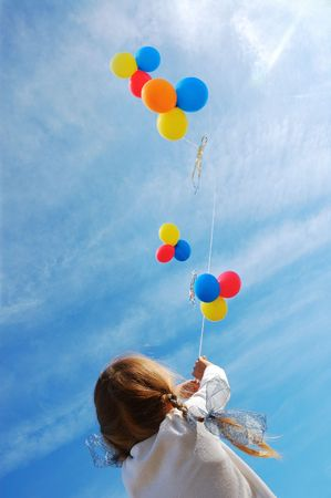 child flying colorful balloons in the blue sky photo
