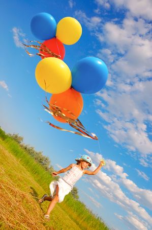 game play: child running with a bunch of colorful balloons in the meadow Stock Photo