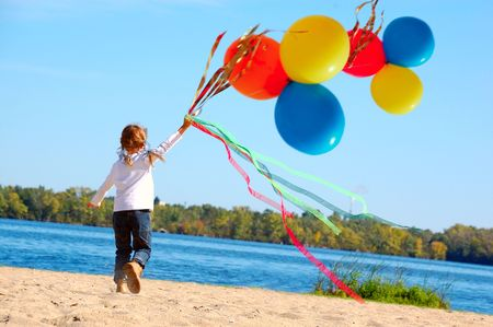 little gile running along the beach with ribbons and balloons