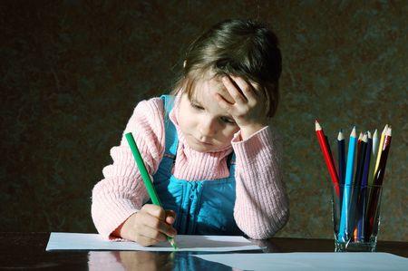 deberes: chica ittle pensativo, sentado en la mesa y hacer sus deberes