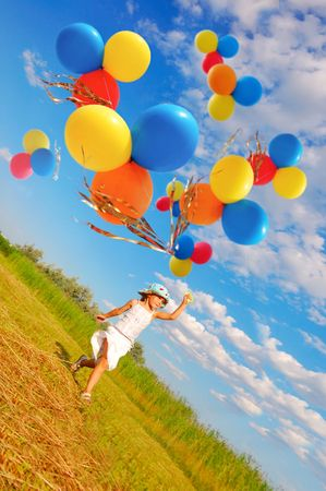 courageous: child running with a bunch of colorful balloons in the meadow Stock Photo