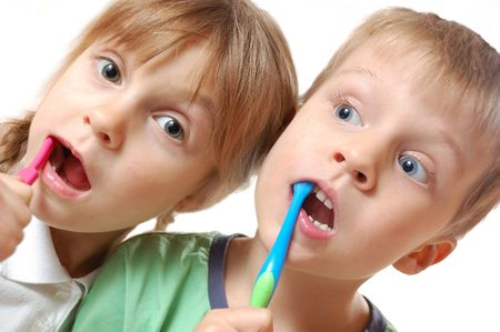 two cute kids brushing their teeth over white background photo
