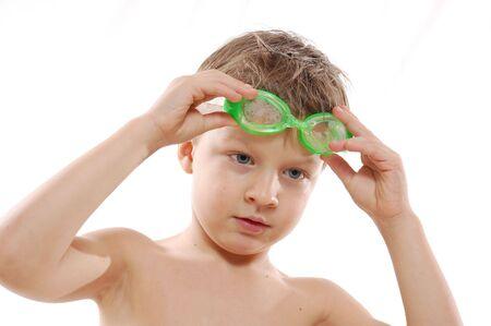 ni�o sin camisa: sonriente edad elemental de ni�o, con el pelo mojado y gafas protectoras sobre blanco