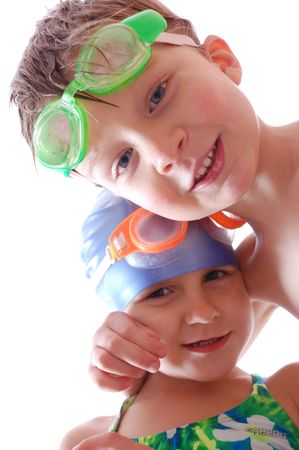 swim goggles: Two happy kids with goggles on their heads. Focus is on the boys face.