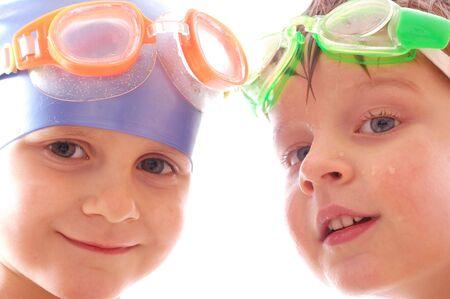 swim goggles: dos ni�os concentrados con gafas en sus cabezas Foto de archivo
