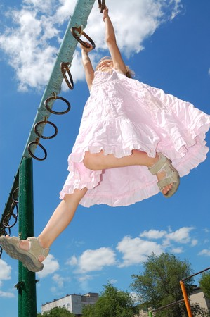 little town:  5 year old girl hanging on gymnastic rings at a storts ground