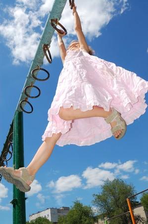 storts グラウンドで体操リングに掛かっている 5 歳の女の子