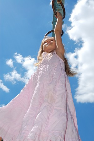 5 year old girl hanging on gymnastic rings moving along the monkey bars against the blus sky Stock Photo - 7146550