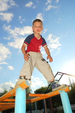 concentrated 7 year old boy standing on monkey bars  photo