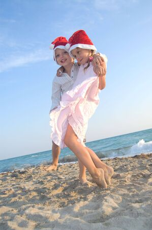 happy 5-6 year old boy and girl with Santa hats playing at the beach Stock Photo - 7298449