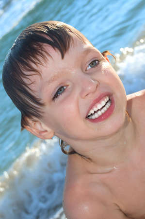 portrait of a happy smiling boy swimming in waves photo