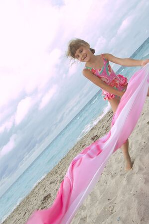 little girl playing with a cloth at the beach photo