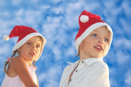 happy 5-6 year old boy and girl with Santa hats against the blue summer sky photo