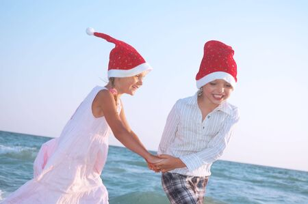happy 5-6 year old boy and girl with Santa hats dancing on the beach photo