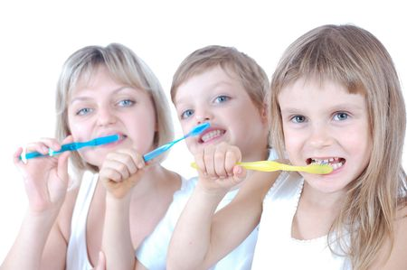 Two childrenand mother cleaning  teeth over white background. Shallow field of depth. The focus is on the girl with a yellow toothbrush. Stock Photo