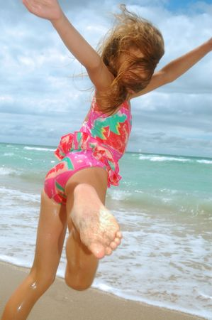little girl playing and dancing at the beach photo