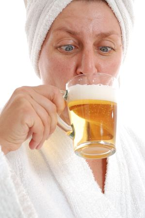 40 year old: 40 year old woman drinking beer in sauna. Isolated over white.