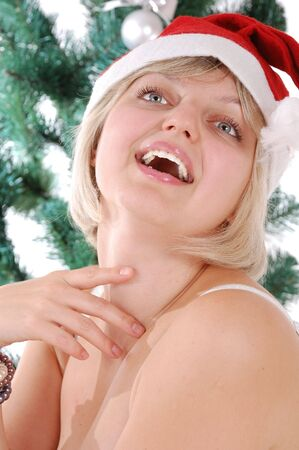 saxy: portrait of a young beautiful blond Caucasian woman agaisnt a Christmas tree Stock Photo