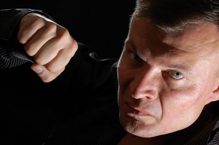 hate: close-up studio portrait of a middle-aged angry man ready for boxing Stock Photo