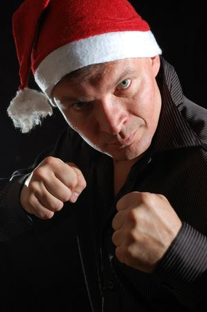 manhood: portait of a man with a Santa hat and fits ready to fight Stock Photo