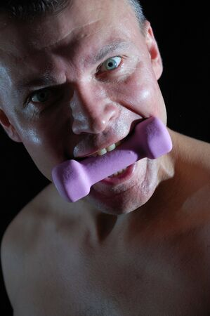 close-up studio portrait of a man with a dumbbell in his mouth photo