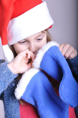 little girl wearing a red Santa hat looking for a present in a Christmas blue sock photo