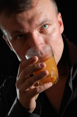 close-up studio portrait of a middle-aged handsome man drinking juice photo