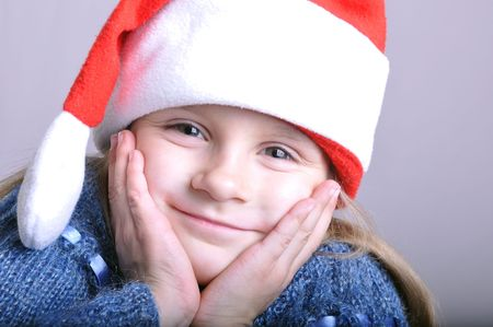 santa clause hat: little happy girl wearing a Santa Clause hat Stock Photo