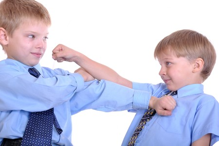 Two schoolboys fighting. Isolated over white. photo
