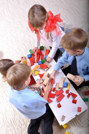 group of happy 3-7 year old kids playing on the floor with wooden blocks photo