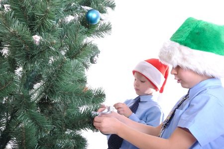 foretaste: Two boys decorating a Christmas tree. Isolated over white. Stock Photo