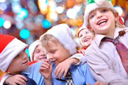 group of happy kids with Santa hats against lights background photo