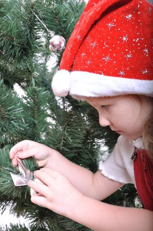 Happy smiling kid in Christmas costume preparing the Christmas tree photo
