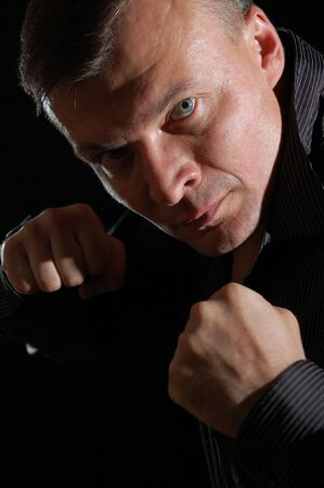 manhood: close-up studio portrait of a middle-aged angry man ready for boxing Stock Photo
