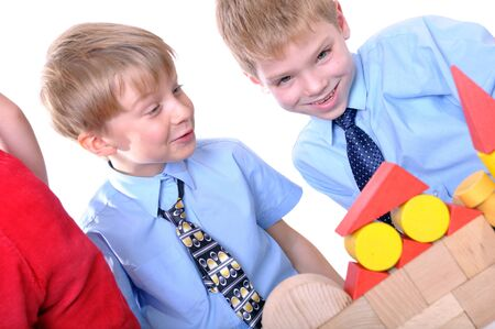 two  boys wearing shirts and ties playing with toy wooden bricks Stock Photo - 8317673