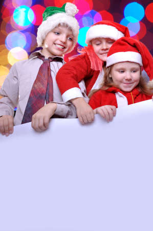 group of happy kids with Santa hats and a big banner photo