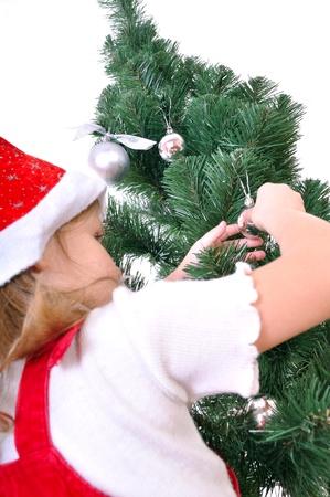 little girl in Christmas costume preparing the Christmas three Stock Photo - 8376577