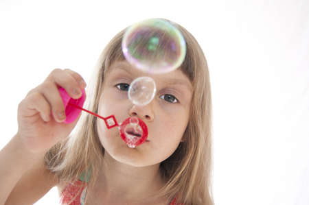 blowing out: Little girl playing with bubble wand.Isolated over white. Stock Photo